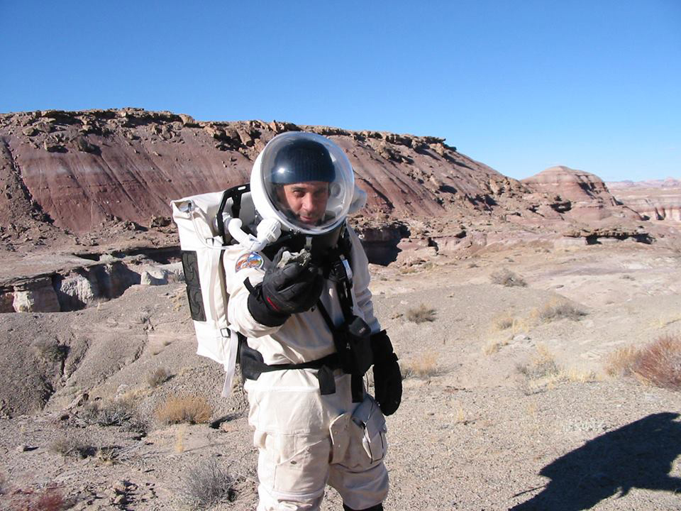 Mars Society founder Robert Zubrin in 2002 holding a dinosaur fossil found while simulating the geological exploration of Mars.  Credit:  Mars Society