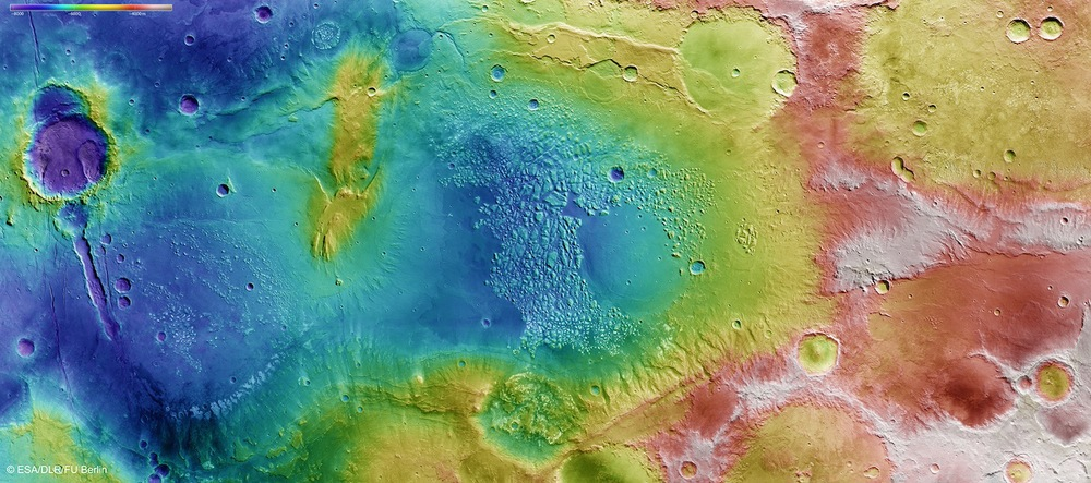 The low-lying Atlantis Basin has been eroded by impact craters and, possibly, ancient water flows. This image from Esa's Mars Express orbiter shows the changing height of the Martian landscape from low lying basins (blue, purple) to peaks and highlands (red, white).  Credit:  ESA/DLR/FU Berlin (CC BY-SA 3.0 IGA)
