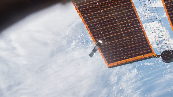 The student-built satellite AAUSat-5 drifts past the International Space Station's solar panels. The satellite will test technology to make maritime travel safer and more efficient.  Credit: Nasa