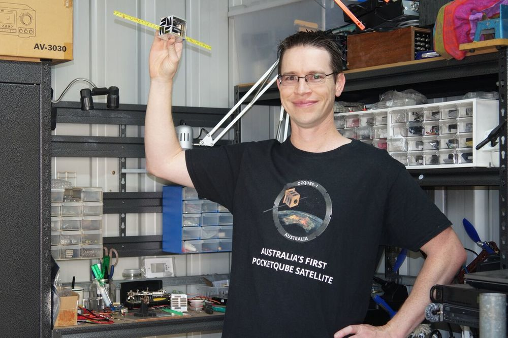 Stuart McAndrew holds a prototype of OzQube-1 in his backyard workshop. The PocketQube's small size, combined with modern electronics, promises to make small remote sensing satellites affordable to amateur satellite makers.  Credit: Stuart McAndrew