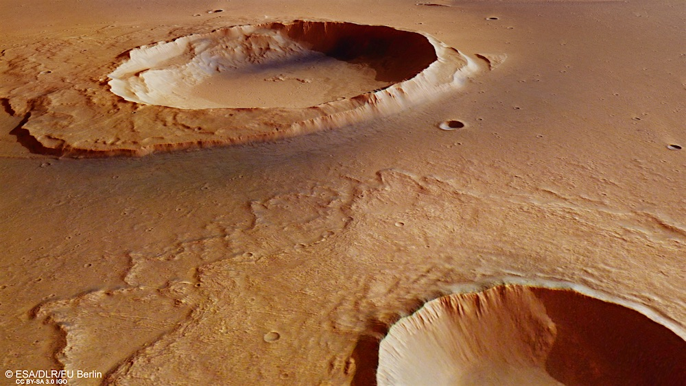 The background crater in Kasei Valles shows debris downstream from an ancient flood while the foreground crater shows signs of impact splashes.  Credit: ESA/DLR/FU Berlin CC BY-SA 3.0 IGO