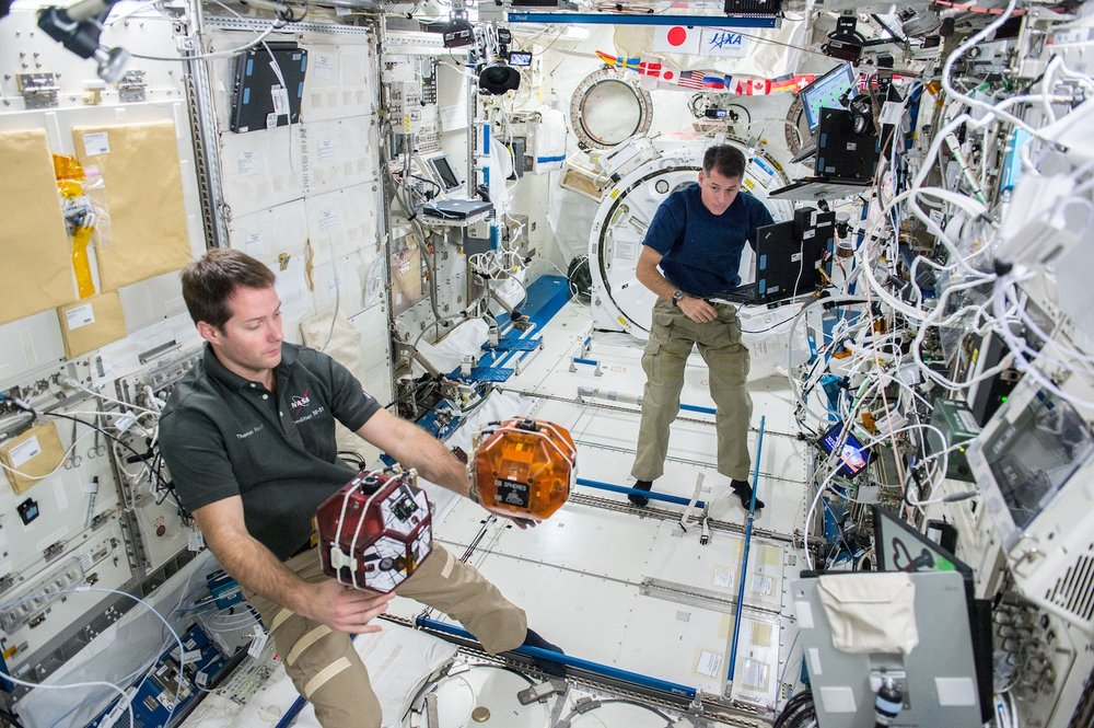 The Spheres robots are working tools on the International Space Station. This picture shows a recent test of space tether technology. Every summer middle school students across the United States get a shot at controlling the robots in the Zero Robotics competition.  Credit: Nasa