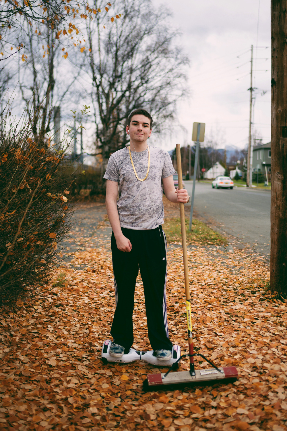 West High School Senior, Paul Marsch, raking leaves on his Hoverboard in South Addition, Anchorage. October 2015.