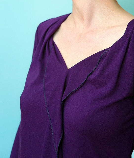 Pleated neckline falls into front flounce, edges finished with a narrow 3-thread overlock