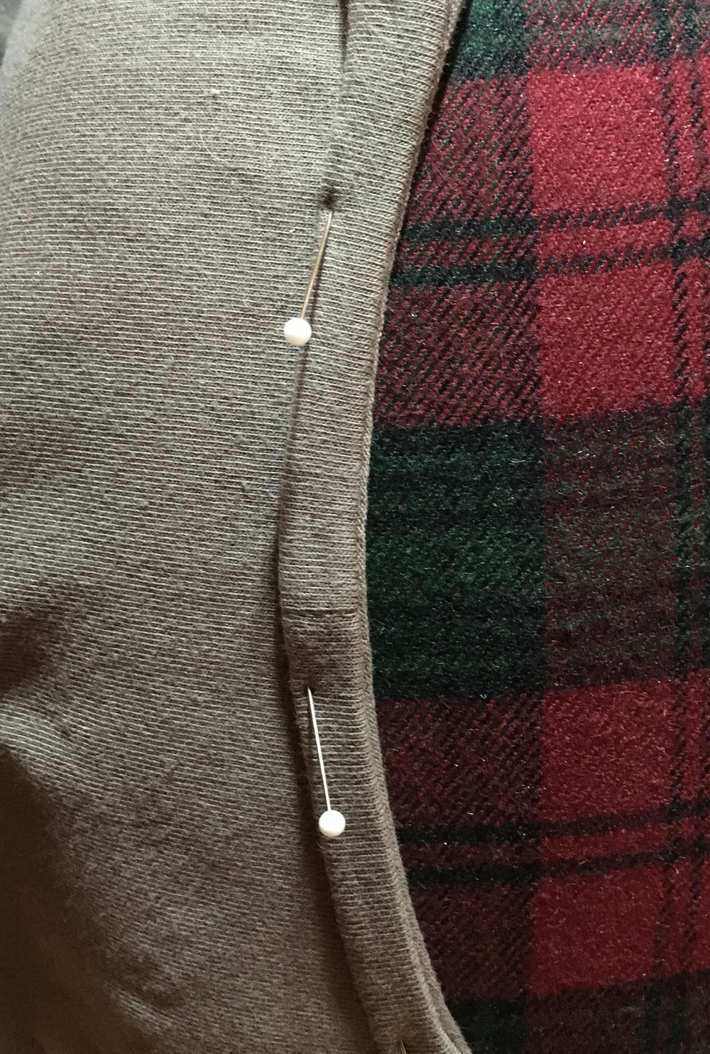 Unfinished edge of facing strip gets turned under seam allowances on right side of garment.
