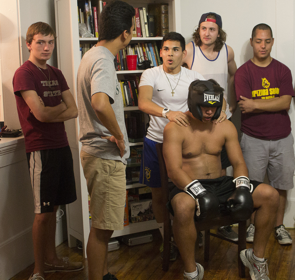 Students prepare for a night of boxing using wrist wraps for extra strength and protection.