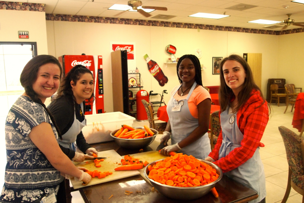 Right to Left: Rebecca, Kyra, Carolyn, and Anna cutting vegetables donated to the little sisters after a collection run.