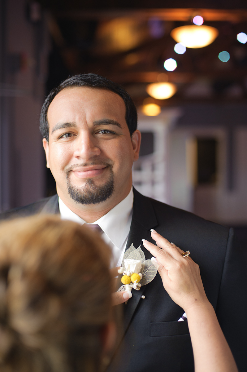 Groom with his mother putting on boutonniere.