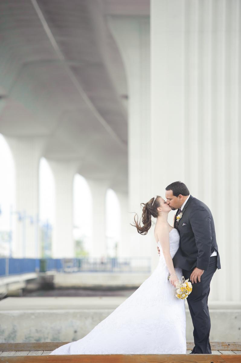Bride and groom kissing under bridge.