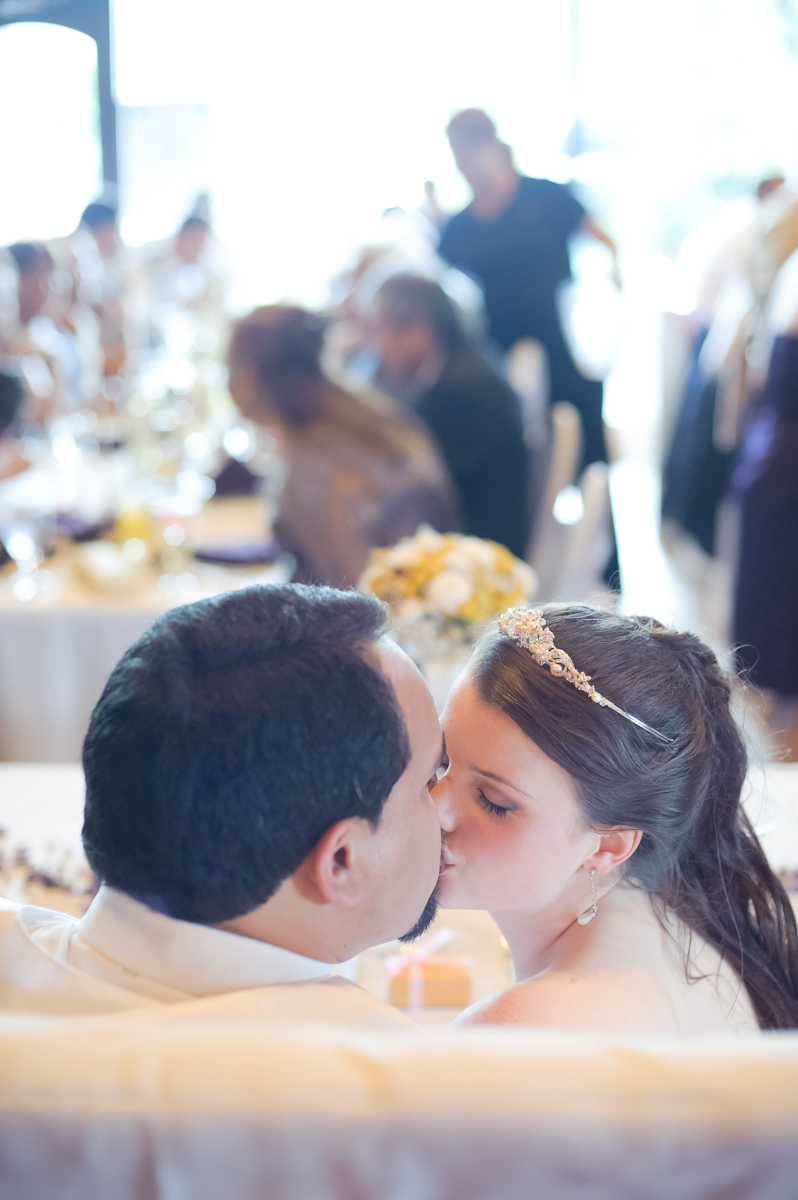 Bride and groom kissing at table.