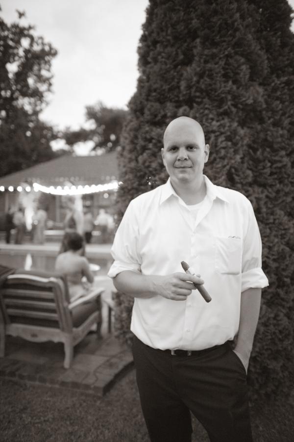 Groom holding cigar by pool.