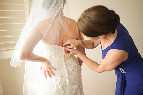 Mother buttoning bride's wedding dress.