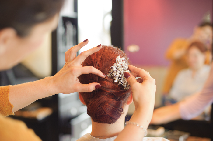 Bride getting hairpin placed by hair stylist.