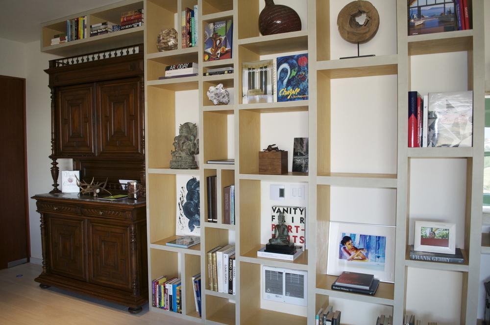 LIBREROS DE IMPACTO - Este librero, de 6 metros de largo, fabricado en madera con frentes de piel cosidos a mano, es definitivamente el elemento clave en el departamento.