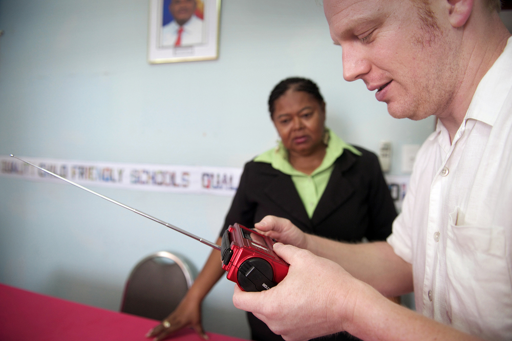 Ears to Our World  founder Thomas Witherspoon demonstrates a self-powered radio at Belize Ministry of Education offices, Belize City.