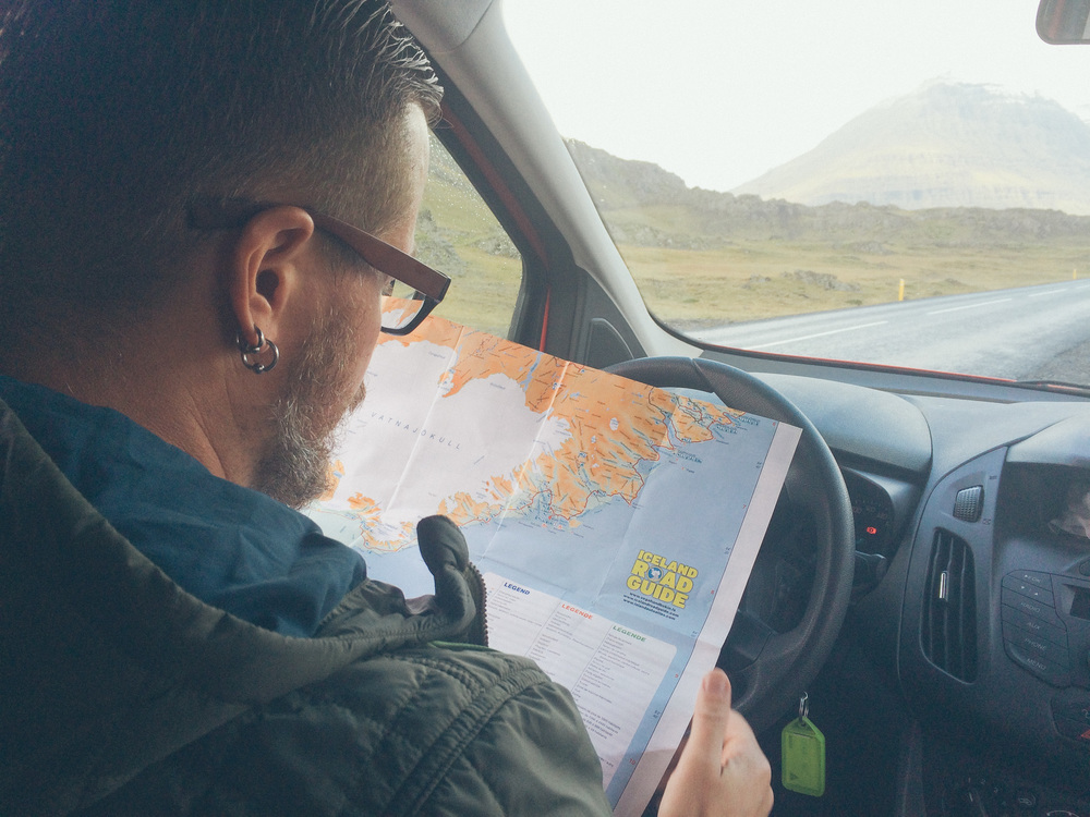 checking a road map while driving the Eastern Coast of Iceland.