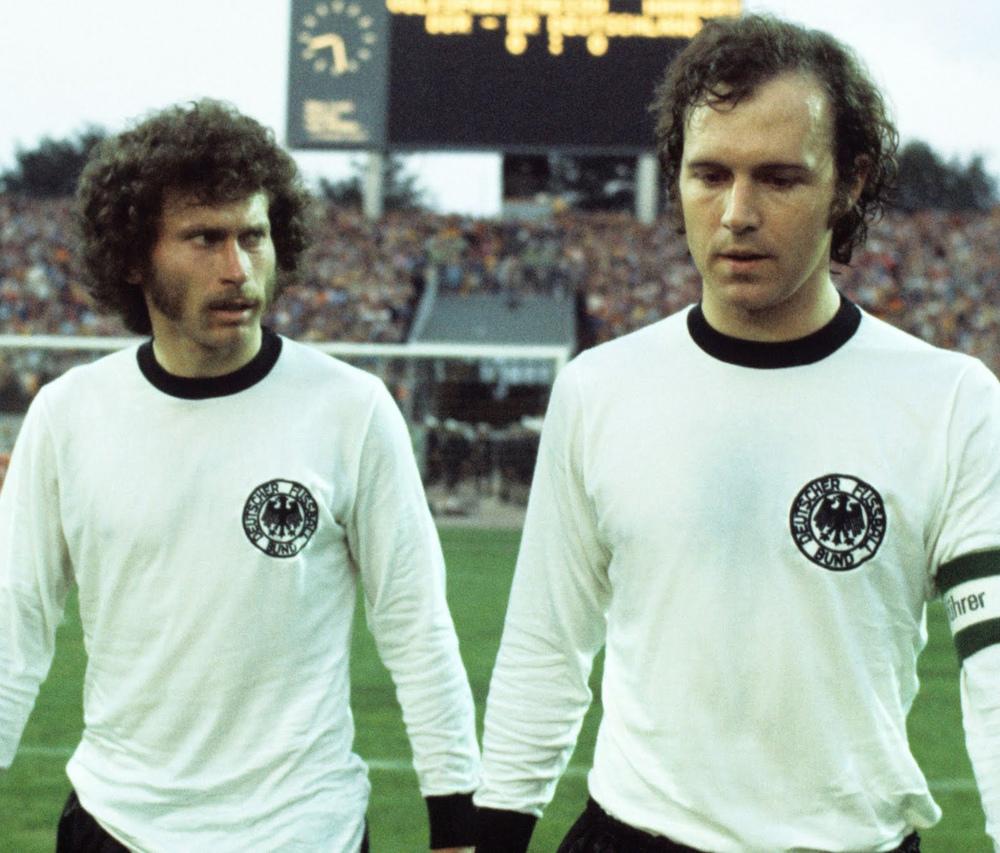 7# Alemanha Ocidental 1974. Outra que coroou o belo uniforme com o título de campeã mundial foi a Alemanha de Beckenbauer e cia. Minimalista, toda branca e com as golas e punhos em preto, a Alemanha vestiu, em casa, um dos uniformes mais clássicos da história do futebol e que até hoje dita o padrão dos alemães.