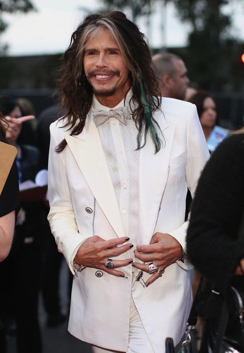 Steven Tyler é um cara conhecido por seus figurinos exagerados e nada convencionais. Na noite de ontem, o cara usou a sua personalidade para combinar um smoking todo branco. Não foi uma boa ideia. Ainda mais se contarmos as unhas pintadas e a mecha branca.