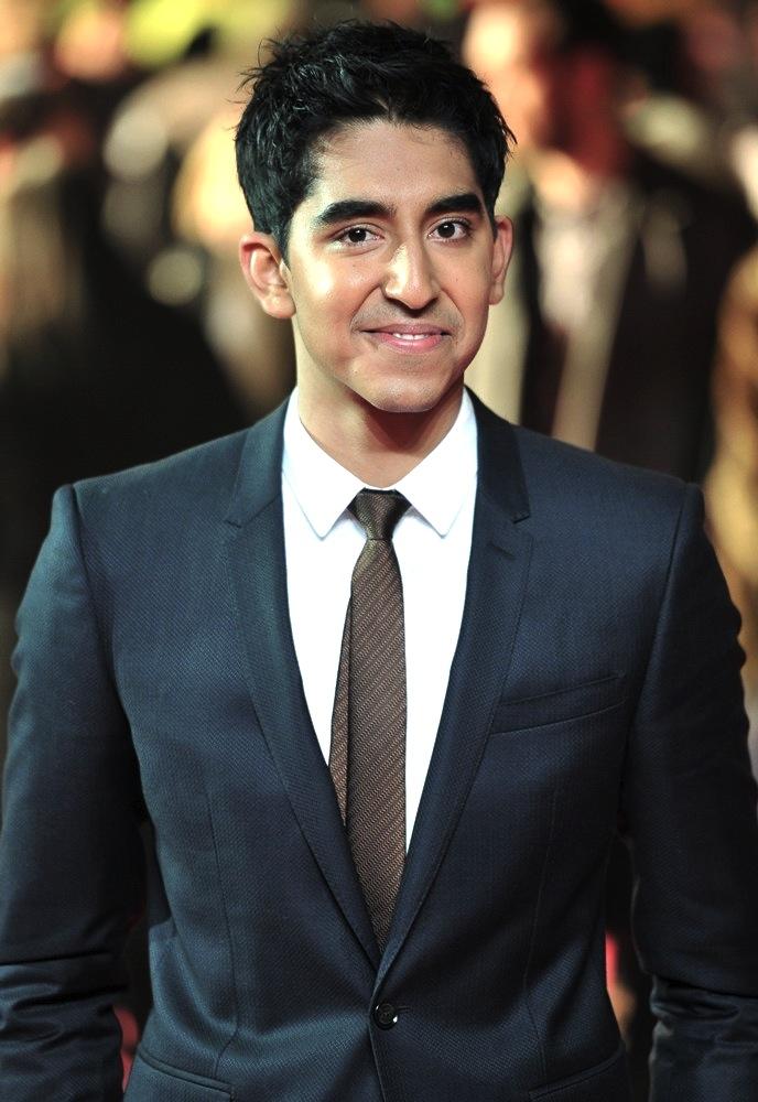 """Dev Patel, diferente do que indica o nome, é um ator inglês de enorme futuro. No cinema e na moda. Sua origem britânica faz com que suas escolhas sejam sempre elegantes, ricas em alfaiataria e detalhes discretos como sapatos, gravatas e óculos escuros. Quem lembra de seu personagem em """"Quem Quer Ser um Milionário"""", engana-se ao pensar que o estilo indiano, cheio de brilhos, cores e etc faz parte do figurino diário do ator. Pelo contrário. Apontado pela revista GQ como um dos ingleses mais bem vestidos de 2013, Dev mostra que a idade, 24 anos completados hoje, e as feições asiáticas em nada influenciam no seu visual."""