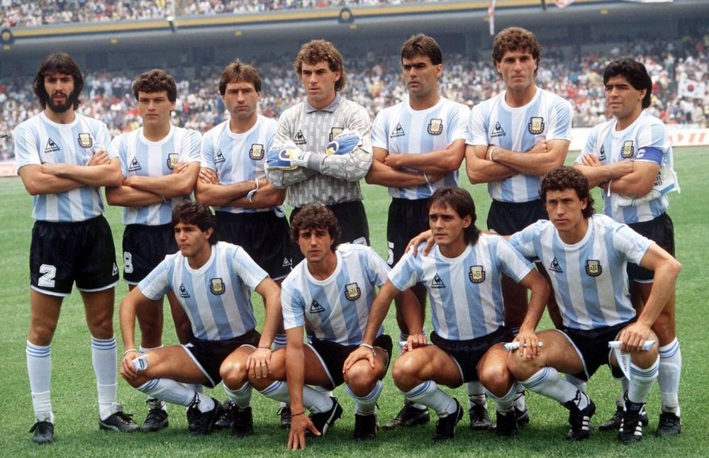 México, 1986. Maradona lidera a Argentina em uma campanha praticamente impecável. No uniforme, as tradicionais listras azuis e brancas, que dessa vez aparecem mais claras, muito mais discretas. No peito, a tradicional grife Le Coq Sportif e um dos uniformes mais bonitos da seleção.