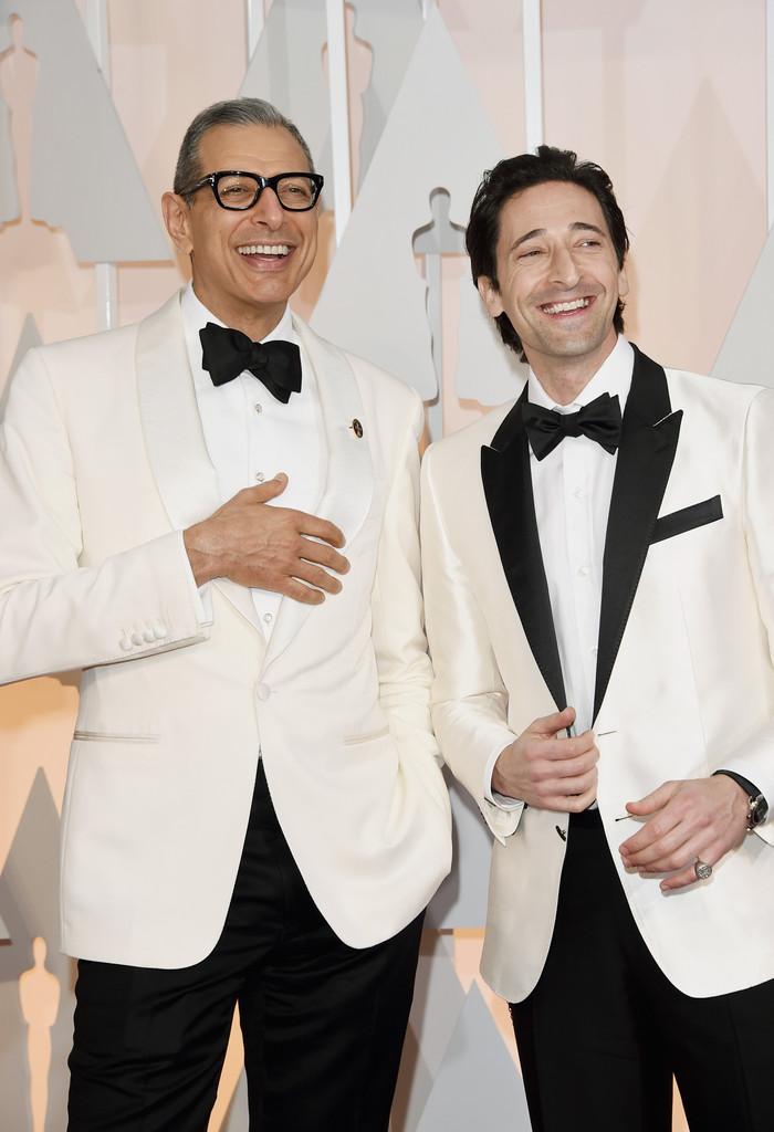 """E o branco reinou mesmo no tapete vermelho do Oscar. A dupla Jeff Goldblum e Adrien Brody, de """"Grande Hotel Budapeste"""" também seguiram a linha. O primeirode forma mais sábia, pois pesou menos nos detalhes responsáveis por chamar muita atenção. Coisa que Brady mostrou menos cuidado ao vestir um blazer com detalhes em excesso na lapela e no bolso."""