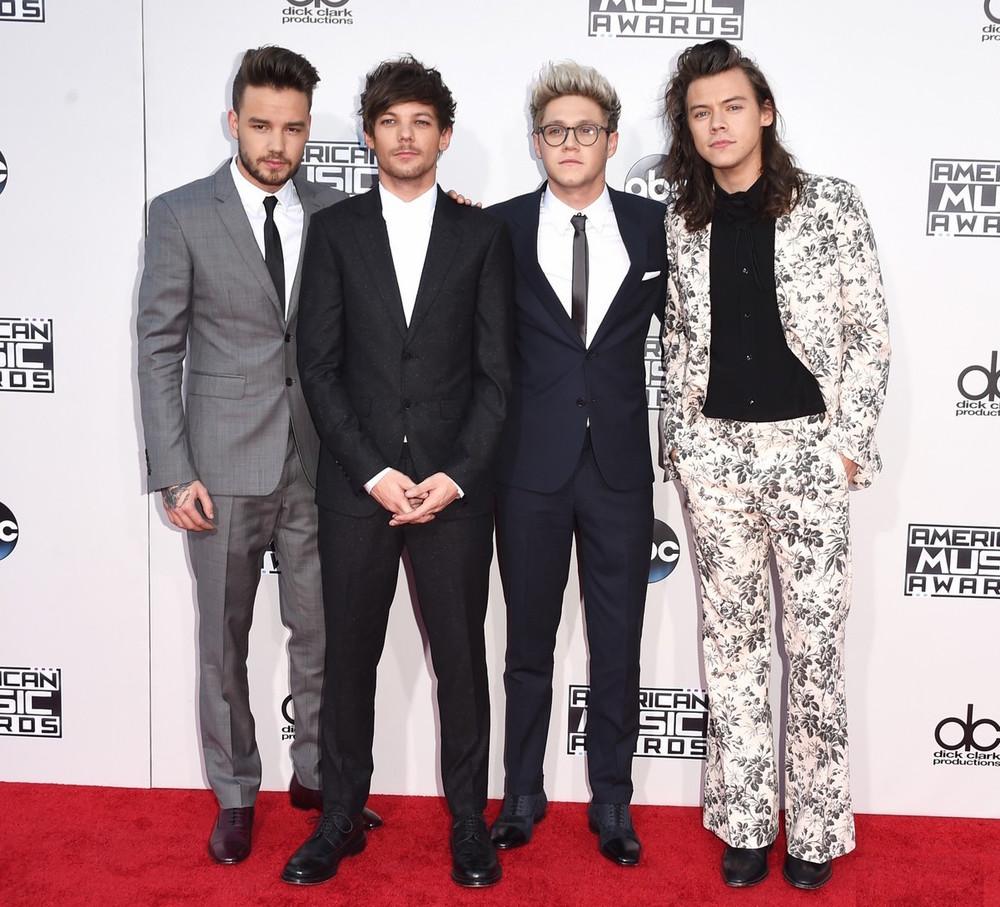 """Vencedores na categoria """"Artista do Ano"""" (não julguemos), os britânicos do One Direction estiveram quase impecáveis no tapete vermelho americano. Quase graças ao integrante da extrema direita, Harry Styles. A estampa até é interessante, mas para uma camisa, lenço ou gravata. Um terno, ainda mais com o corte folgado na calça, foi exagero. De resto, tradições britânicas devidamente seguidas."""