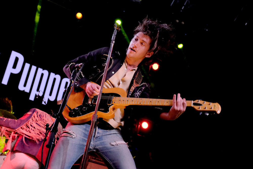 Alex Turner - The Last Shadow Puppets Enquanto na semana passada ele vestiu um traje laranja, nesse fim de semana, Alex Turner optou por uma abordagem mais rock 'n' roll. Camisa aberta, calça surrada e todo aquele pacote que já conhecemos.