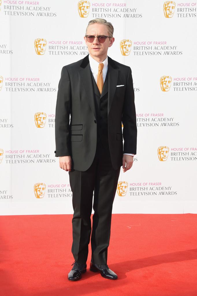 Martin Freeman Com um interessante costume de três peças, sendo um colete com lapelas e uma bela gravata. Destaque para o óculos modelo 'club master'.