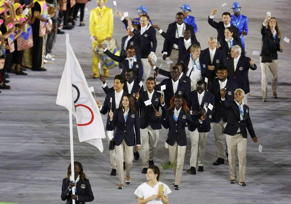 Time Olímpico de Refugiados Uma das delegações mais ovacionadas da noite, o Time de Refugiados contou também com um uniforme simpático. Blazer marinho com calça bege. Já comentamos por aqui que essas cores combinam e os atletas acima deixaram isso bem claro.