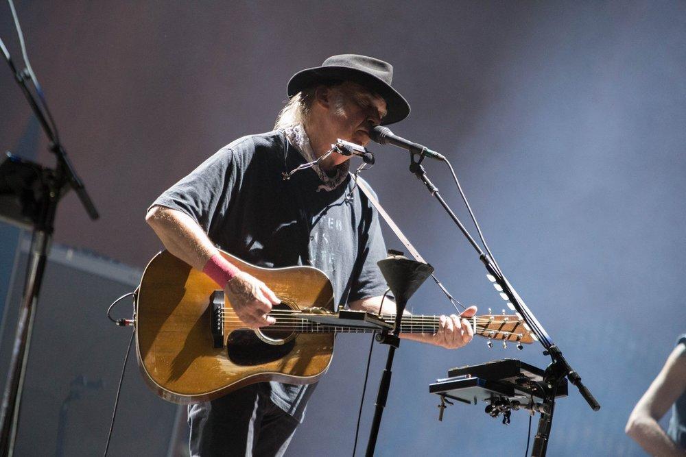 """Neil Young Incorporando o seu mais tradicional estilo que mistura rock'n'roll com as suas raízes rurais, o cantor canadense fez questão de mais uma vez levantar a sua bandeira em favor do meio ambiente. Dessa vez a mensagem veio por meio de uma camiseta surrada (ao melhor estilo Neil Young) com os dizeres """"Água é vida""""."""