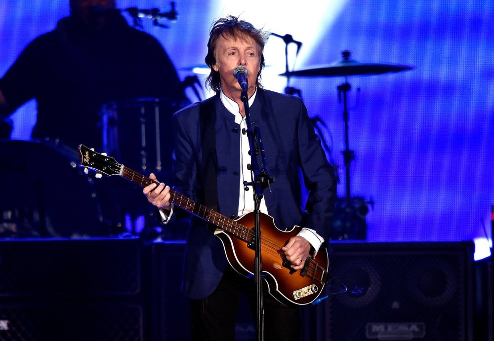 Paul McCartney Encabeçando a nossa galeria, Paul trajou o seu habitual blazer de gola padre azul marinho. Uma camisa de colarinho tradicional faria um papel melhor por baixo, mas quem somos nós para discordar de Sir McCartney. Percebam como azul e marrom combinam muito bem no contraste do blazer com o contrabaixo Hofner.