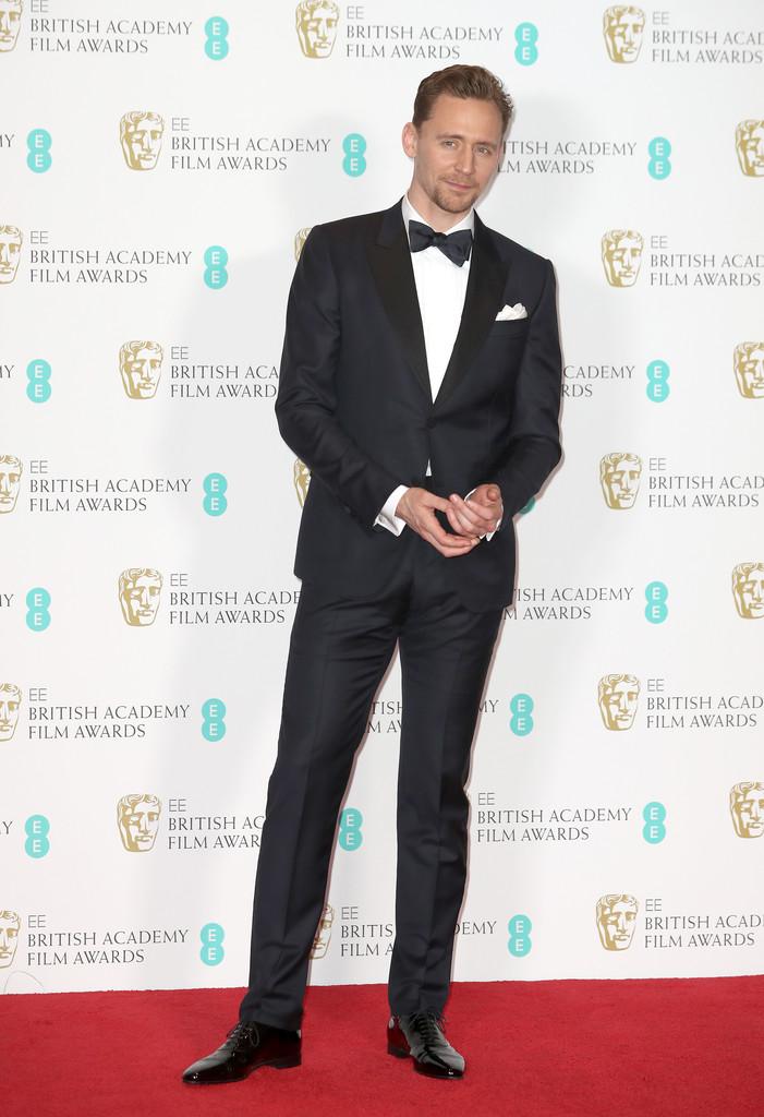 Tom Hiddleston Outro  hors concours . Tom Hiddleston e a sua enorme habilidade para se vestir retornam ao nosso convívio. Dessa vez num traje marinho, de lapelas pretas em ponta. Destaque para as abotoaduras e o lenço do bolso.