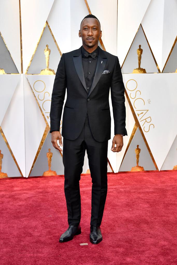 """Mahershala Ali Vencedor na categoria de Melhor Ator Coadjuvante pelo filme """"Moonlight"""", o americano encerra a nossa galeria com um terno (com colete) que é um primor de tom sobre tom. Medidas perfeitas e apenas acessórios pontuais. Digno de prêmio mesmo."""