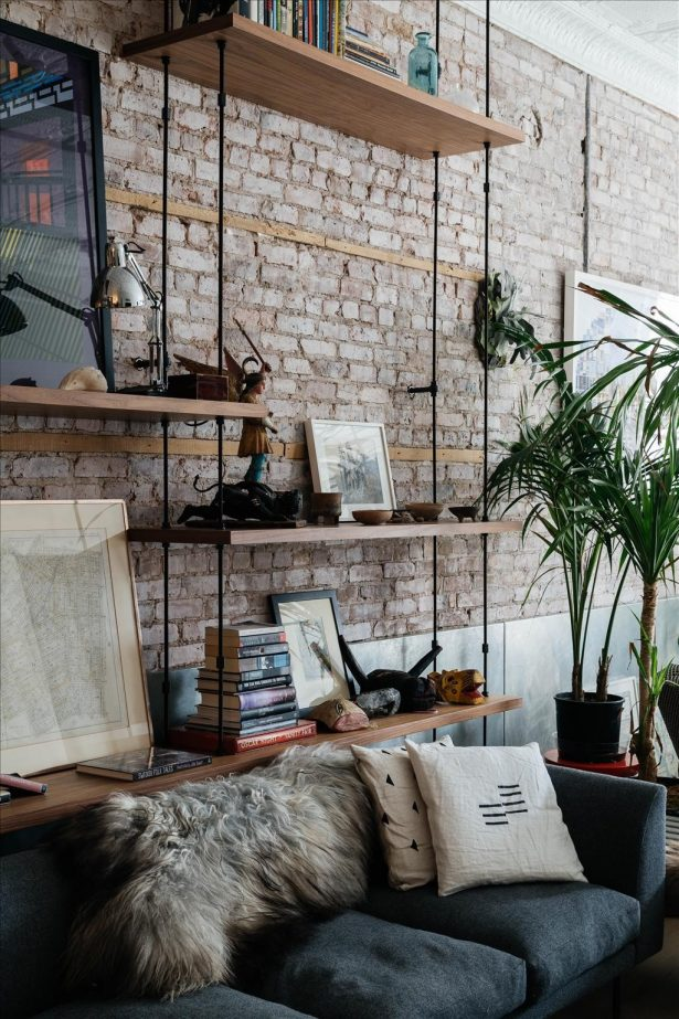 brown-brick-wall-wooden-rack-black-couch-white-cushion-sofa-home-decor-accent-red-book-black-painting-metal-swing-arm-desk-light-green-plant-615x923.jpg