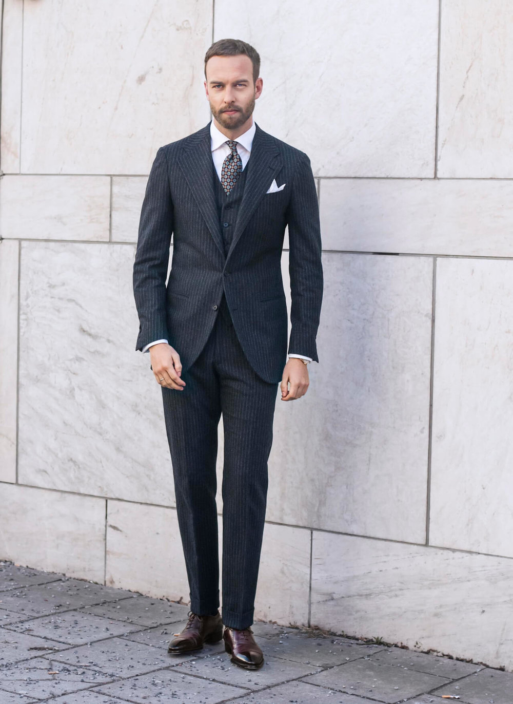 Modern-cut-three-piece-suit-with-simple-white-linen-pocket-square-and-printed-tie.jpg
