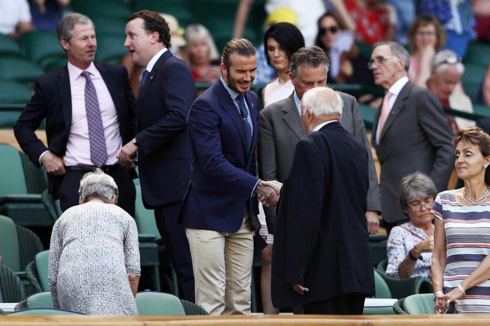David Beckham Outro habitué do torneio, Beckham sabe como poucos encarar o  dress code  de Wimbledon. Reparem como o azul do blazer se repete na gravata e na camisa. Isso se chama sabedoria. E como já falamos aqui, também se chama  roubar cor . A calça de outra cor deu uma quebra elegante e totalmente adequada para o conjunto.