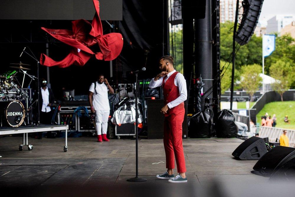 Jidenna Dos cantores de hip hop mais elegantes da atualidade,Jidenna, que na foto aparece se despindo do paletó, foi mais uma vez destaque. Com um terno de três peças vermelho, ele nos fez lembrar como é bacana quebrar paradigmas de gêneros e estilos - é raro vermos rappers vestindo ternos e gravatas. Destaque para a quebra também evidenciada no calçado.