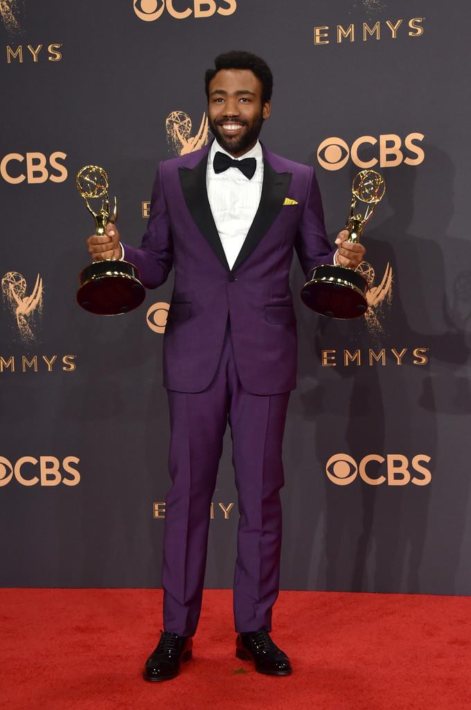 Donald Glover Mais uma vez premiado, o rapper/ator foi também um dos destaques em termos de figurino. Com um smoking azul de lapelas pretas, acessórios discretos e um penteado interessante, o rapaz mais uma vez entra na lista dos mais elegantes da noite.