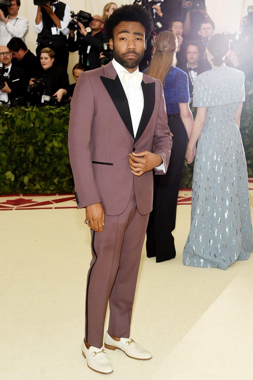 Donald Glover Fechando a nossa galeria, um dos rappers mais bem vestidos da atualidade. Também conhecido como Childish Gambino, Glover acertou nas cores, no penteado e na barba. O sapato branco poderia ser substituído por um modelo preto mais discreto e a gravata poderia ser diminuída praticamente pela metade.