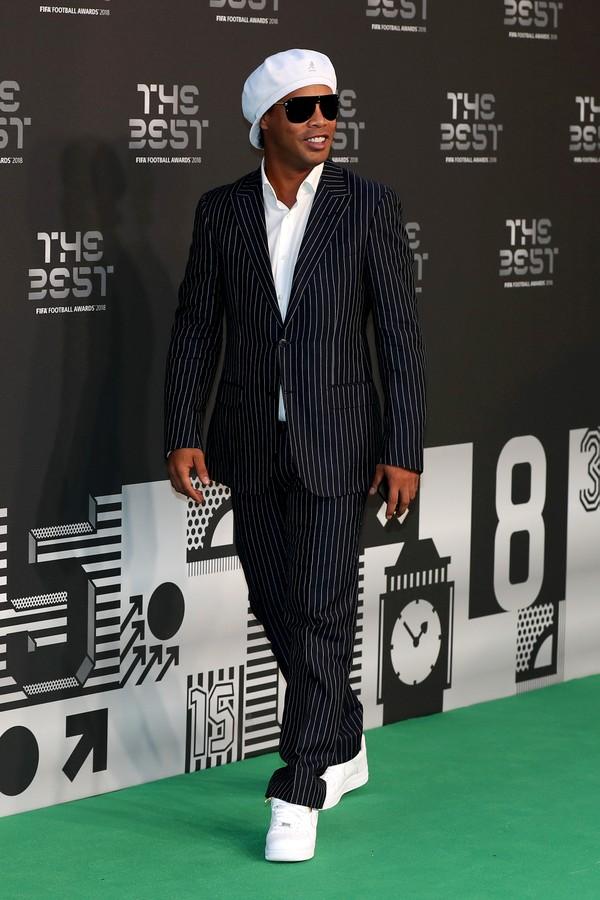 """Ronaldinho Gaúcho Naquele seu já tradicional estilo, o """"bruxo"""" dispensou a gravata e o sapato para investir em um figurino mais no seu feitio. Não vamos negar que a originalidade é um fator fundamental na hora de se vestir, mas a boina e o tênis branco foram um certo exagero. De resto, até que o R10 se saiu bem."""
