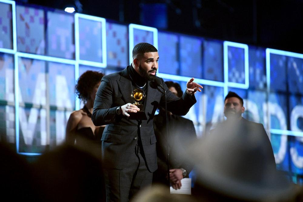 Drake Vencedor na categoria Melhor Música de Rap (God's Plan), Drake subiu ao palco de traje escuro sobre blusa de gola rolê. Elegante, discreto e muito adequado. A corrente dourada para fora poderia ter sido evitada, mas dada a simplicidade do acessório, o figurino merece os nossos aplausos.