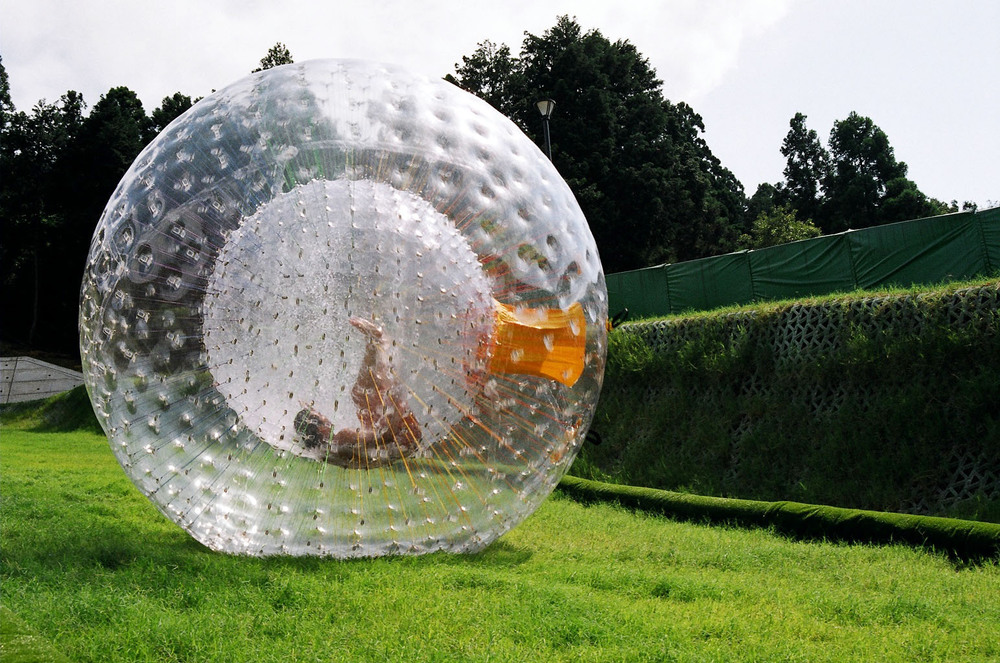 "Zorbing is a sport in which a participant is secured inside an inner capsule in a large, transparent ball that is then rolled along the ground or down hills. It's one of the thrill seeking activities that Mike A has done....swimming with sharks is on his ""to do"" list"
