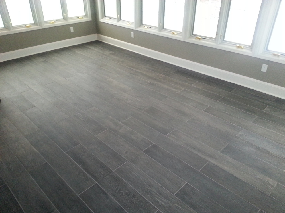Custom sun room with porcelain floor. Installation by Groundswell Contracting