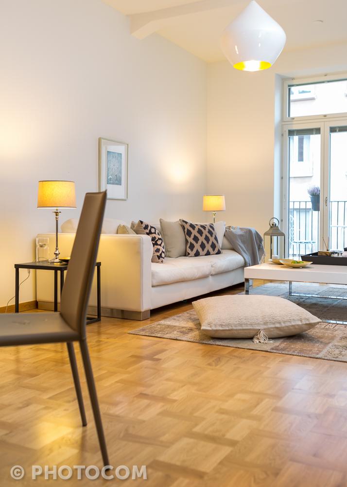 Valantin nahkainen Syli- sohva teetettiin mittatilauksena. Sohvan istuinsyvyyttä lisättiin, joten nyt sohvalle mahtuu vierekkäin makoilemaan. Patinoitunut matto ja lattiatyyny yhdessä kiiltävien modernien pintojen kanssa tuovat tilaan mielenkiintoista jännitettä. Tom Dixonin sisältä kullattu suuri kattovalaisin vangitsee katseen.