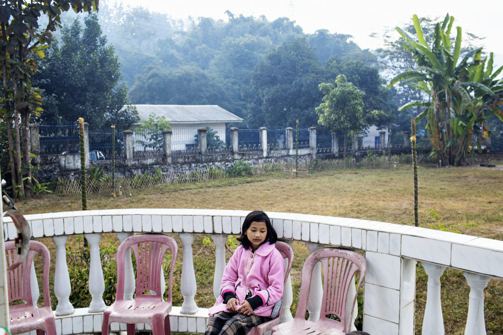 A young girl sit outside a packed church during mass December 30, 2012 at the Roman Catholic church in Laiza, Kachin State in northern Myanmar.
