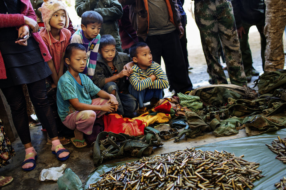 Young Kachin boys look at ammunition and weapons seized from the Burmese Army after the KIA won a battle a few days earlier.