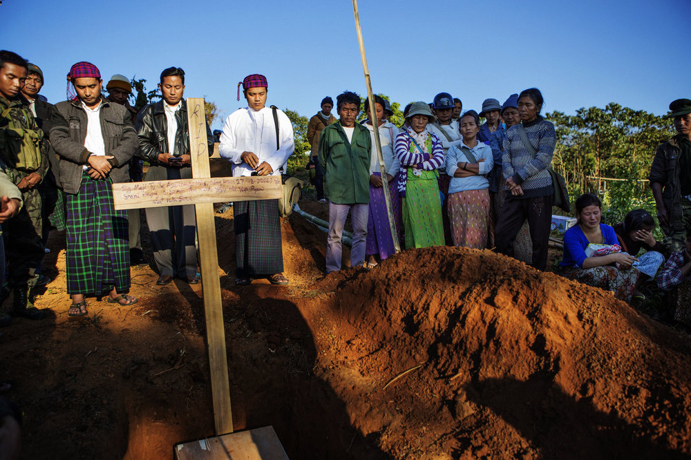 Relatives, Christian Ministers and church members attend the funeral of Maji Tu Ja, 40, who was killed from Burmese Army mortars  whilst repairing his tractor in a field. Three other civilians were wounded in the same attack - two of them seriously.