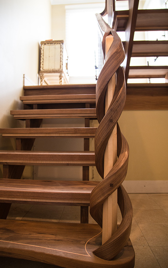 Black walnut and maple twist together in a floating staircase and newel designed by Nathie Katzoff of NK Woodworking | Photo courtesy NK Woodworking