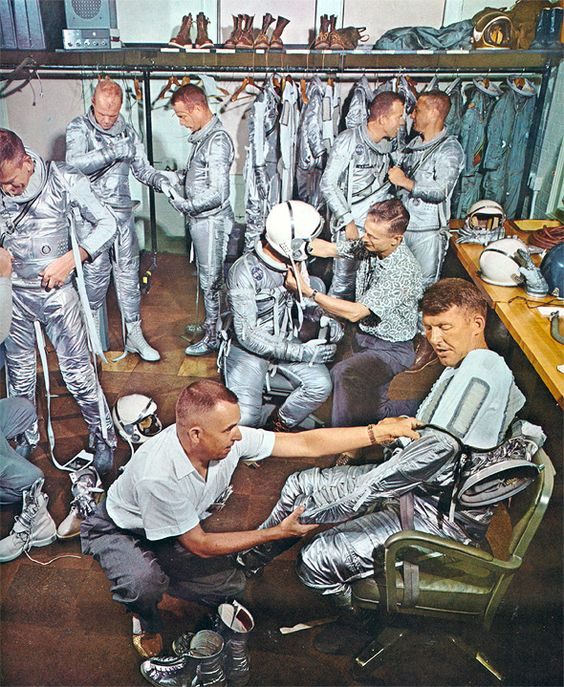 The Mercury 7 in a fitting for their Mark IV space suits. Note the sage green option for the suit in the back right.