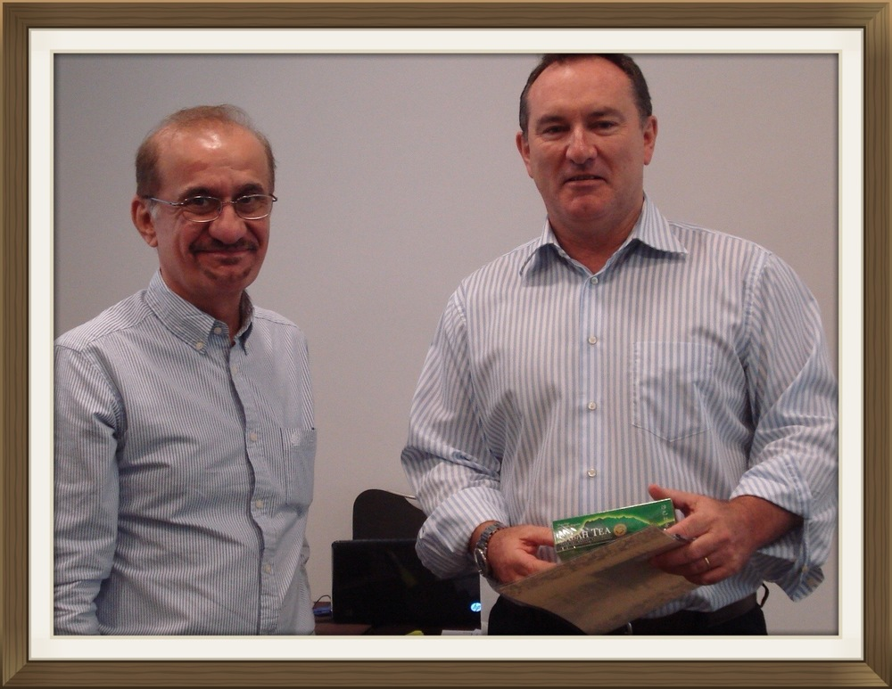 "Peter Attfield - Human Resource Director at Alghanim Industries Kuwait and Ayadh Farooq posing together after receiving his certificate and tea souvenir during the ""How to Improve Your National Development Program Workshop"" held in Dubai"